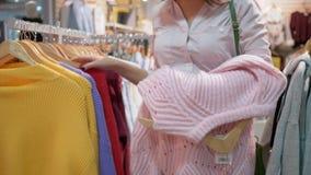 Shopaholism, menina feliz escolhe a roupa nova e pendura-a disponível cabendo na loja da forma durante descontos na alameda filme