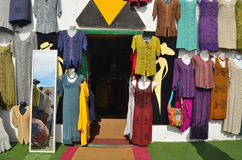 Shopfront with colorful garments hanging on wall and mirror. TEGUISE, LANZAROTE, SPAIN - NOVEMBER 20, 2016: Shopfront with colorful garments hanging on wall and royalty free stock photo