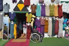 Shopfront con gli indumenti variopinti che appendono sulla parete con la sedia a rotelle ha lasciato esterno ed a specchio Immagini Stock