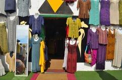 Shopfront con gli indumenti variopinti che appendono sulla parete e sullo specchio Fotografia Stock Libera da Diritti
