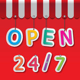 Shopfront sign. Colorful paper open 24/7 signs on red background and awning Stock Photo