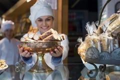 shopgirl aanbiedend luim en biscuitgebak voor verkoop stock foto