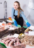 Shopgirl with apron offering fresh fish in shop Royalty Free Stock Photos