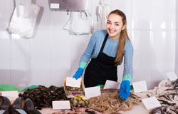 Shopgirl with apron offering fresh fish in shop Stock Photos