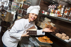 Shopgirl with chocolate and confectionery Stock Images