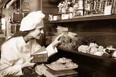 Shopgirl with chocolate and confectionery Royalty Free Stock Photography
