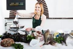 Shopgirl in fresh fish store Stock Image