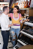 Shopgirl helping man to select synthesisers Stock Photography