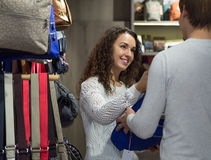Shopgirl helpingman to select handbag in store Stock Image