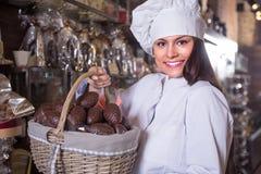 Shopgirl posing with chocolate eggs Stock Photos