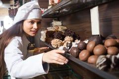 Shopgirl posing with delicious chocolate Stock Photos