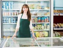 Shopgirl standing near fridge with frozen goods Royalty Free Stock Image