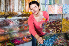 Shopgirl in store is picking up candies Royalty Free Stock Photography