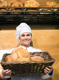 Shopgirl working in bakery with bread and different pastry Royalty Free Stock Images