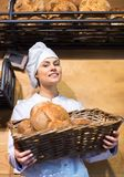 Shopgirl working in bakery with bread and different pastry Stock Image