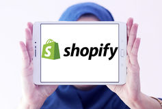 Shopify company logo. Logo of Shopify company on samsung tablet holded by arab muslim woman. Shopify is a commerce platform that allows anyone to easily sell stock photos
