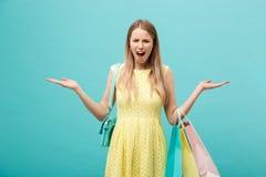 Shoping et concept de vente : belle jeune femme malheureuse dans la robe élégante jaune avec le panier photographie stock
