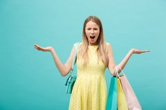 Shoping and Sale Concept: beautiful unhappy young woman in yellow elegant dress with shopping bag. Shoping and Sale Concept: beautiful unhappy young woman in royalty free stock photo