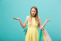 Shoping and Sale Concept: beautiful unhappy young woman in yellow elegant dress with shopping bag. Shoping and Sale Concept: beautiful unhappy young woman in royalty free stock images