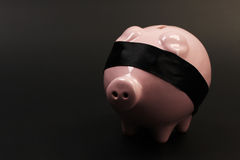 ShoPink piggy bank with black blindfold standing on black background. Pink piggy bank with black blindfold standing on black background - horizontal Royalty Free Stock Photo