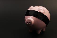 ShoPink-Sparschwein mit schwarzer mit verbundenen Augen Stellung auf schwarzem Hintergrund Lizenzfreies Stockfoto