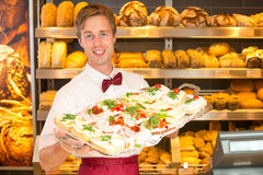 Shopkeeper in baker's shop with tablet of sandwiches Stock Images