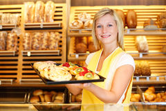 Shopkeeper in baker shop with tablet full of cake Stock Photo