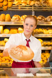 Shopkeeper in Bakery giving bread to customer Stock Photo