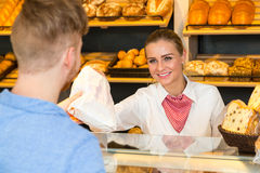 Shopkeeper in bakery hand bag of bread to customer Royalty Free Stock Images