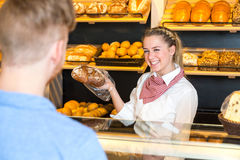 Shopkeeper in bakery presenting loaf of bread to client Royalty Free Stock Photography