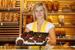 Shopkeeper in bakery presents tablet of rum balls Royalty Free Stock Photography