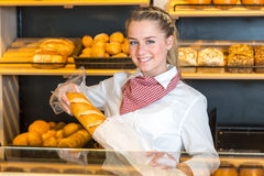 Shopkeeper at bakery putting loaf of bread into paper bag Royalty Free Stock Photo