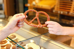 Shopkeeper in bakery sells pretzel Royalty Free Stock Images