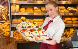 Shopkeeper in bakery showing sandwiches to customer Royalty Free Stock Image