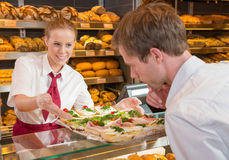 Shopkeeper in bakery showing sandwiches to customer Royalty Free Stock Images