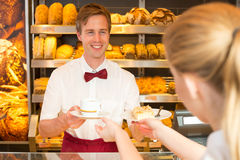 Shopkeeper in cafe giving cup of coffee to client Royalty Free Stock Photography