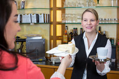 Shopkeeper in confectionery gives client cake and coffee Stock Images