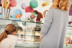 Shopkeeper in confectionery serves girl with ice cream stock photos