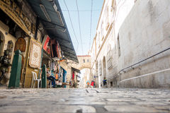 Shopkeeper and tourist on narrow street of Jerusalem Royalty Free Stock Images