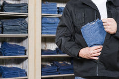Shoplifter stealing denim Stock Image