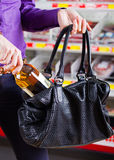 Shoplifting. A female shoplifting or stealing Royalty Free Stock Image