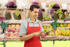 Greengrocer using smartphone. Shopman with apron uses a smart phone at the fruits store Royalty Free Stock Photography