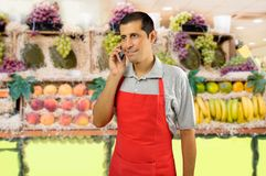 Greengrocer talking by phone. Shopman with apron using a smart phone at the fruits store Royalty Free Stock Photos