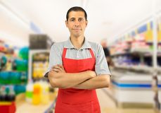 Shopman at the supermarket. Portrait of smiling shopman standing and looking at the supermarket with crossing arms Royalty Free Stock Photo