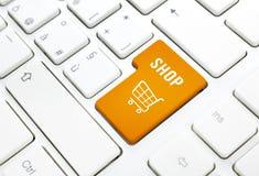 Shoppa affärsidéen. Den orange shoppingvagnen knäppas eller stämm på vit skrivar Arkivbilder