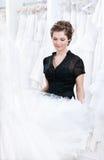 Shoppa assistenten önskar att välja en riktig klänning Fotografering för Bildbyråer
