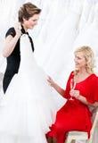 Shoppa assistenten föreslår en bröllopsklänning Royaltyfri Foto