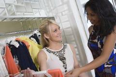 Shoppa assistenten Helping Customer At som kläder shoppar Arkivbilder