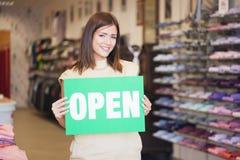 Shoppa assistenten Holding 'det öppna' meddelandet Royaltyfri Foto