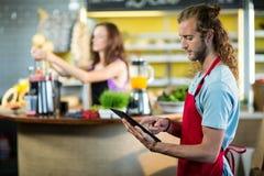 Shoppa assistenten som använder en digital minnestavla i shoppa Royaltyfri Fotografi
